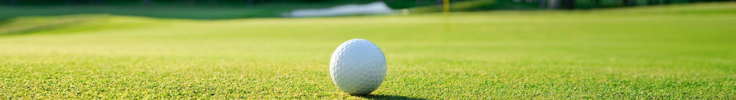 A landscape view of a golf ball resting on top of green grass with a blurred view of the golfcourse.